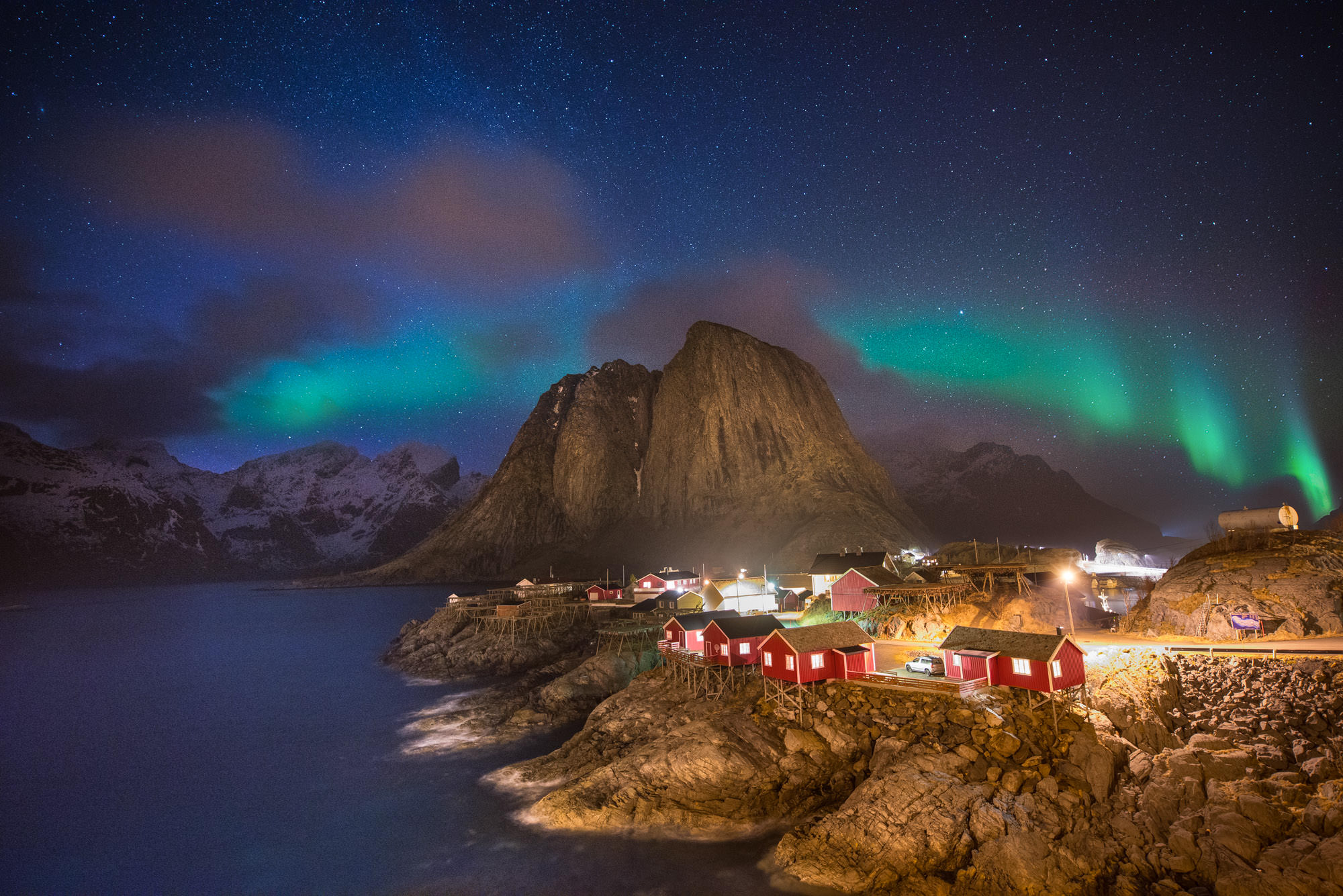 A fishing village with small red houses on the coast in Norway at night with the Northern Lights overhead