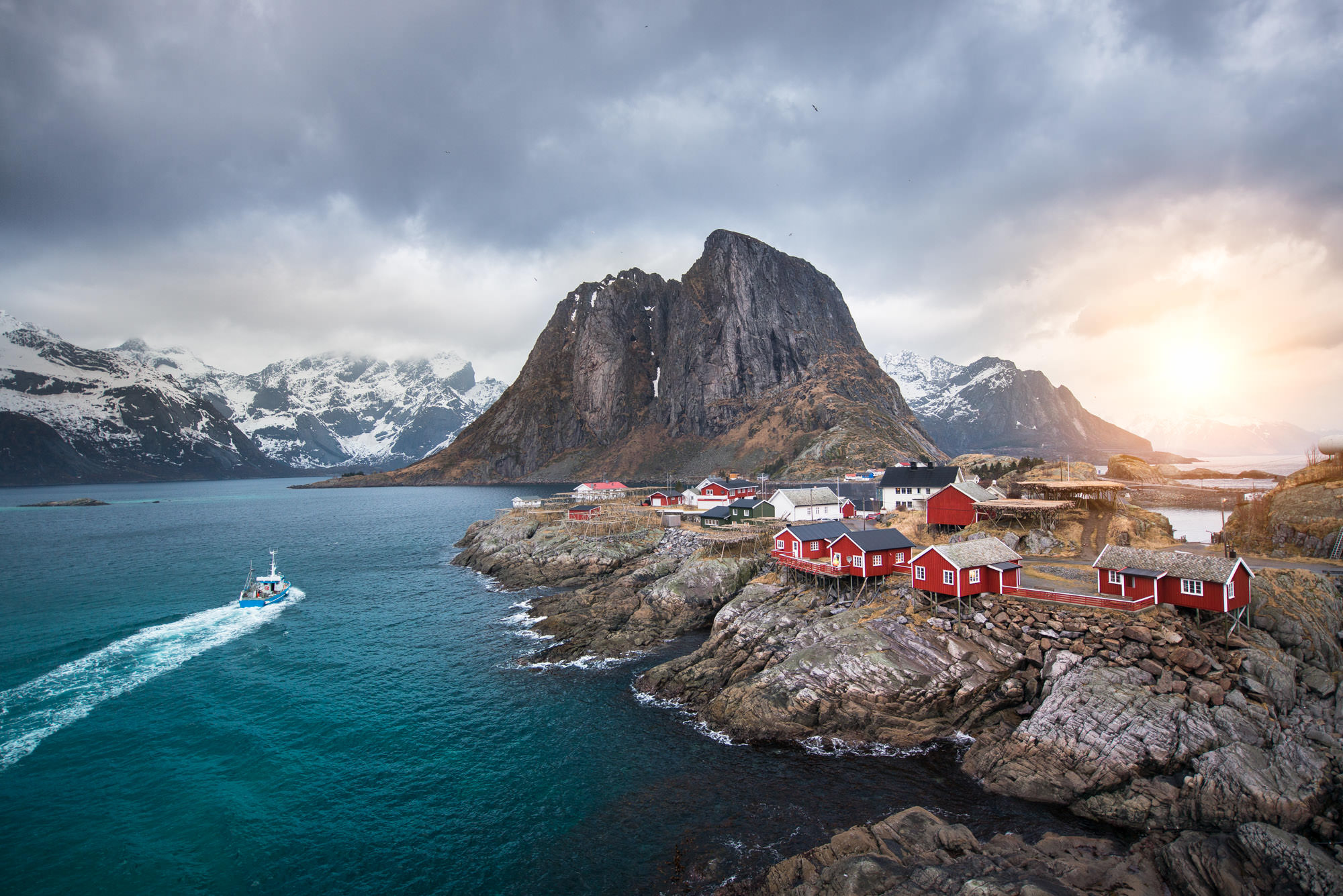 A fishing village with small red houses on the coast in Norway with a boat sailing past.