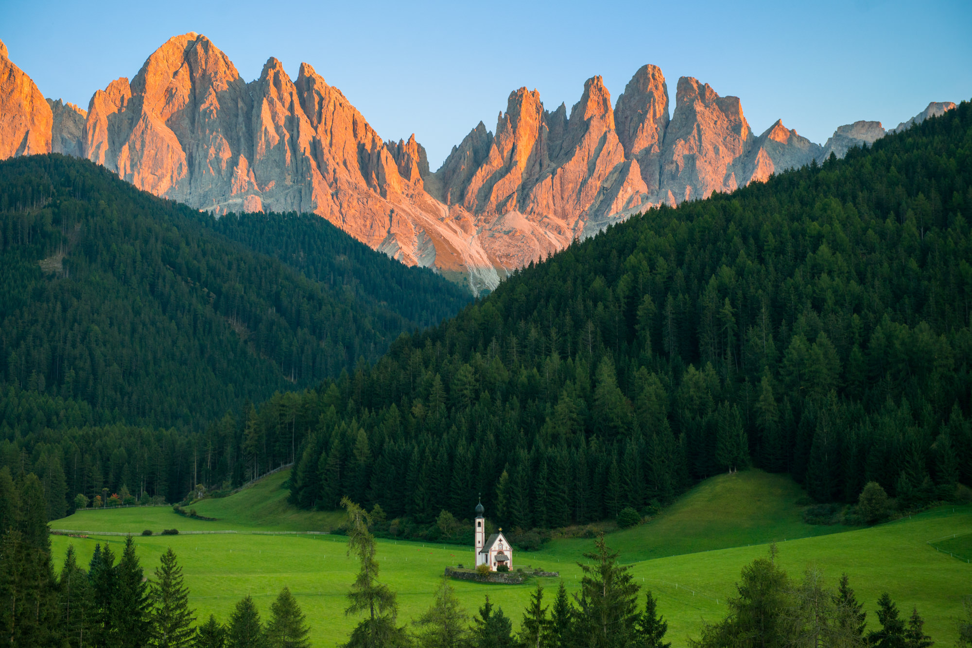 A lone church in a green meadow with huge mountains towering in the distance