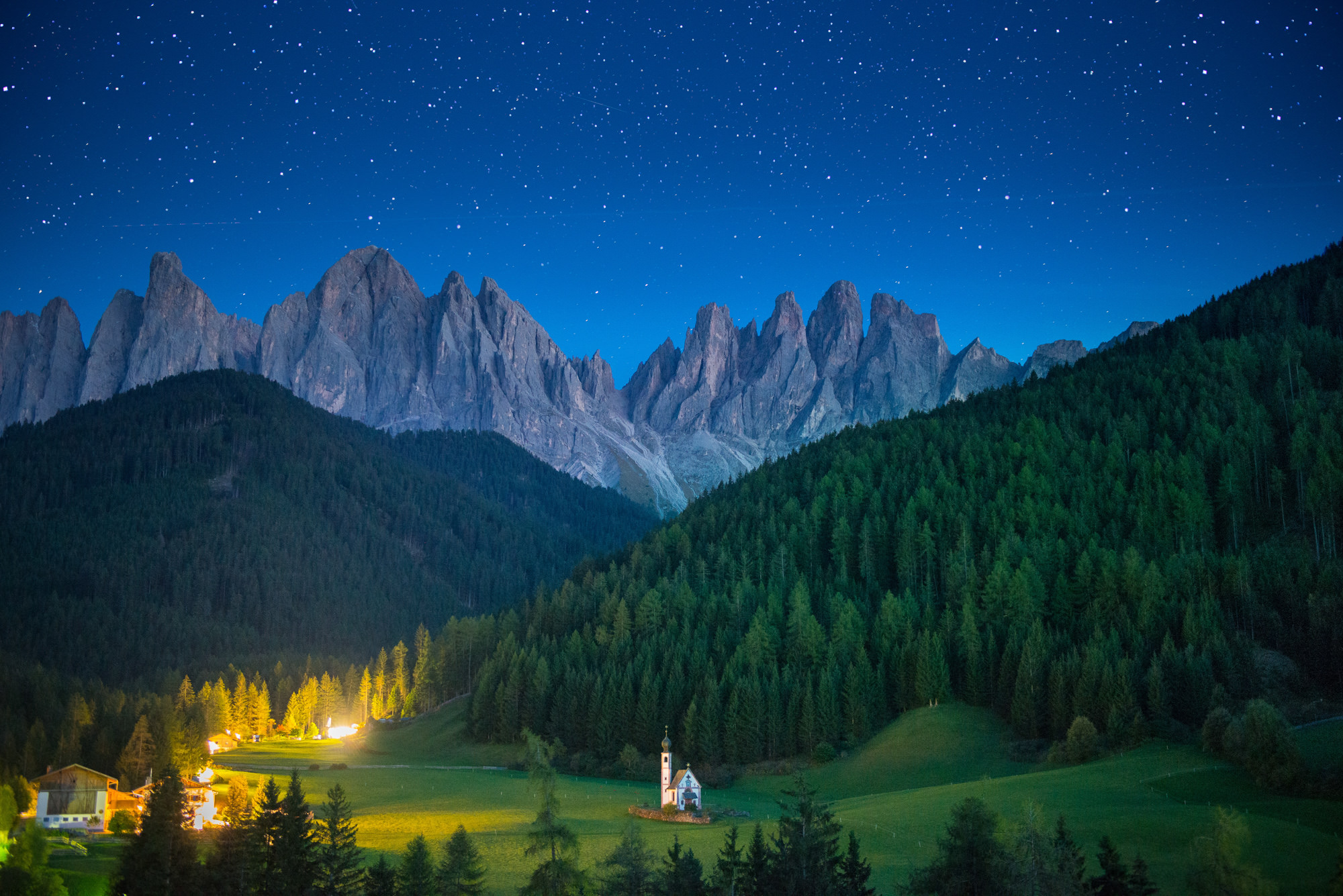 A lone church in a green meadow with huge mountains towering in the distance at night