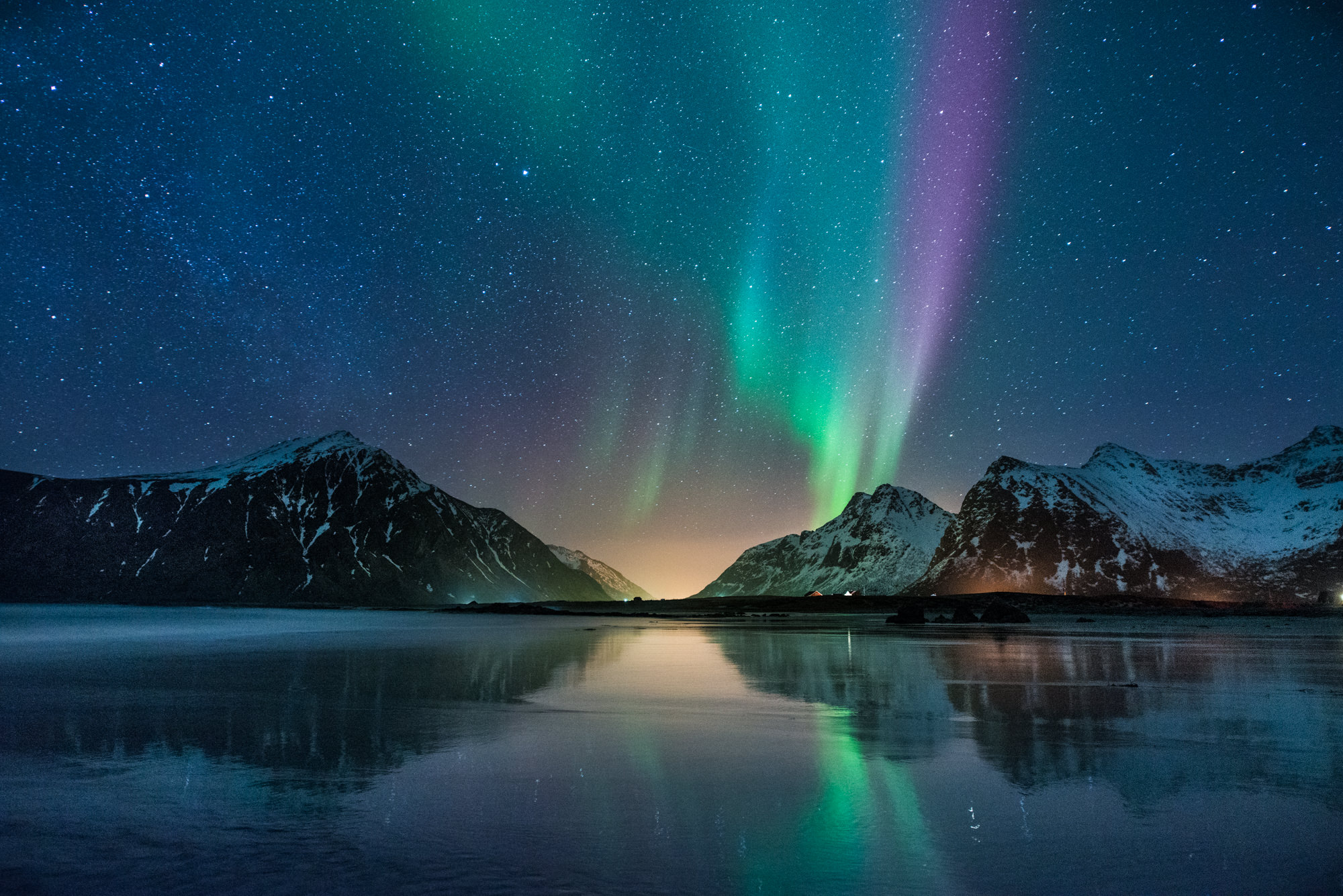 A colourful aurora reflects on the beach in Norway