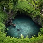 A woman relaxes floating in the To Sua Ocean Trench in Samoa
