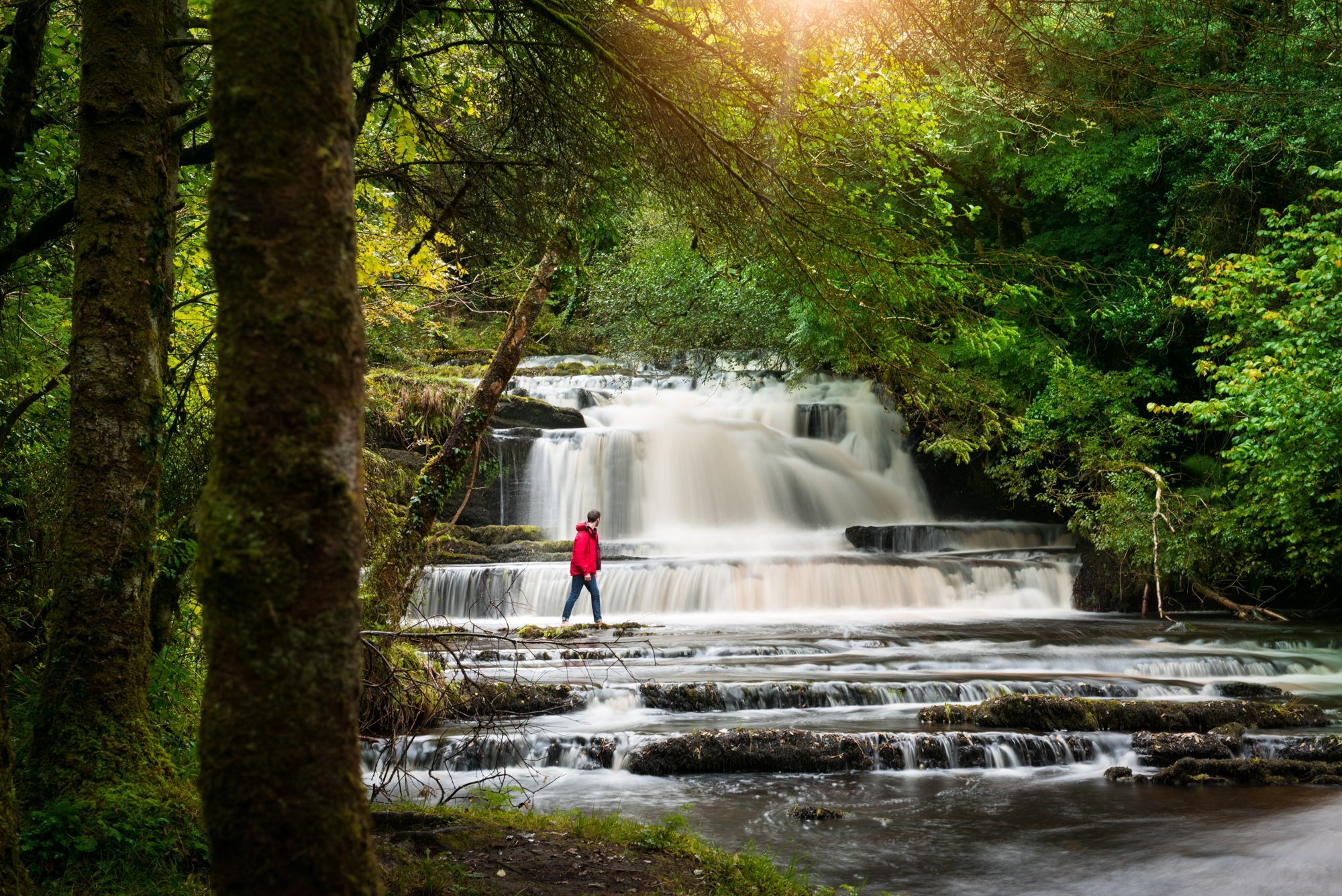 A man looking up at the impressive Fowley Falls