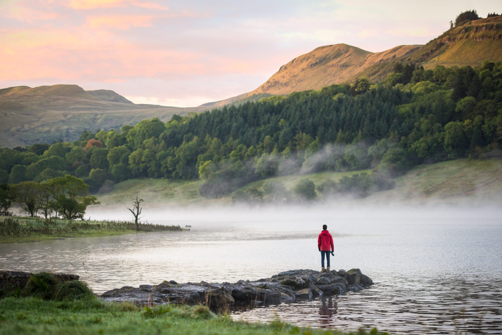 Man looks over misty lake at sunrise with a camera in his hand