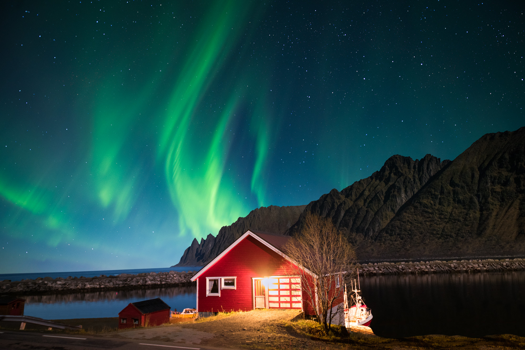 The northern lights dance through the sky above a cabin