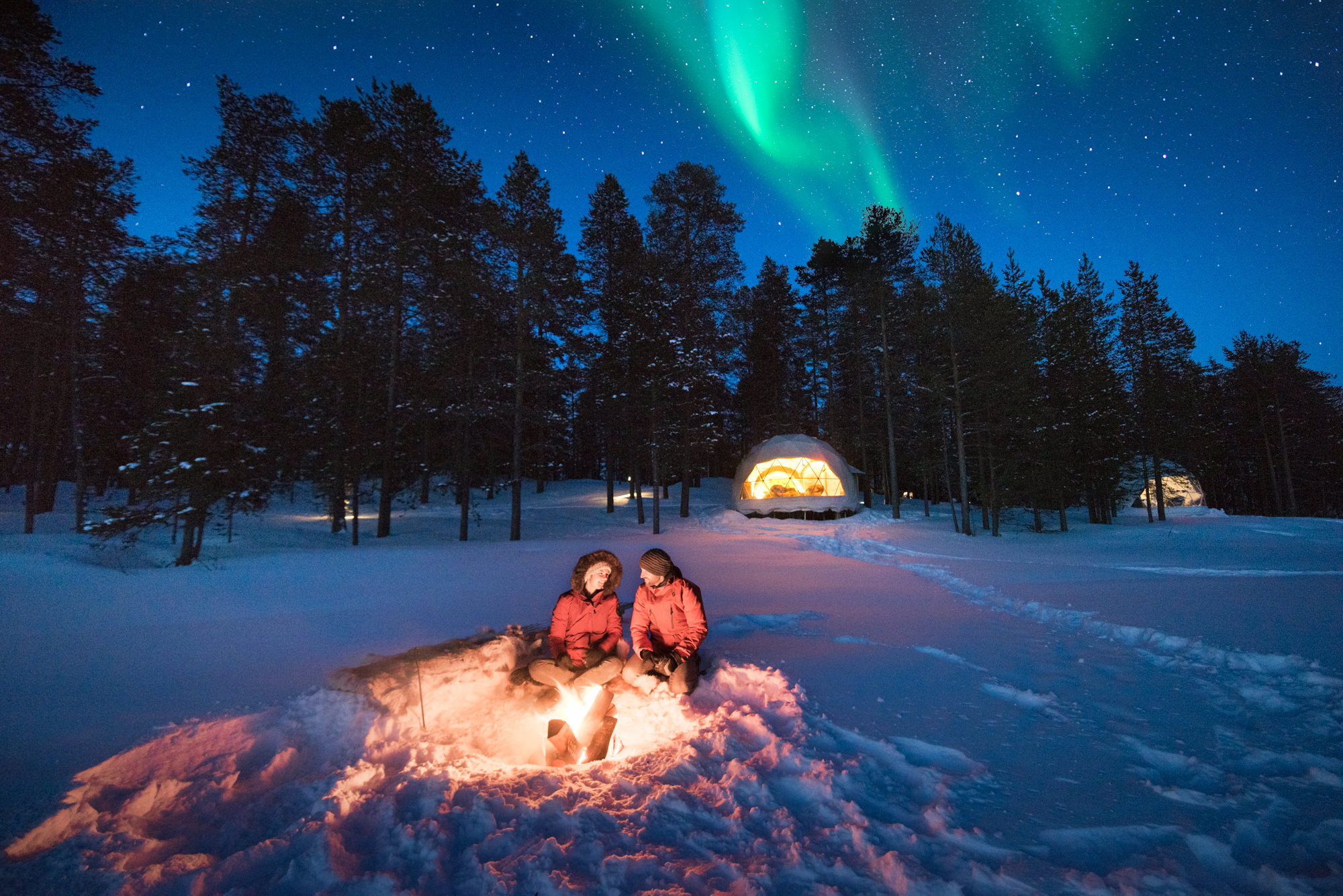 Two people sit in front of a campfire with the aurora overhead