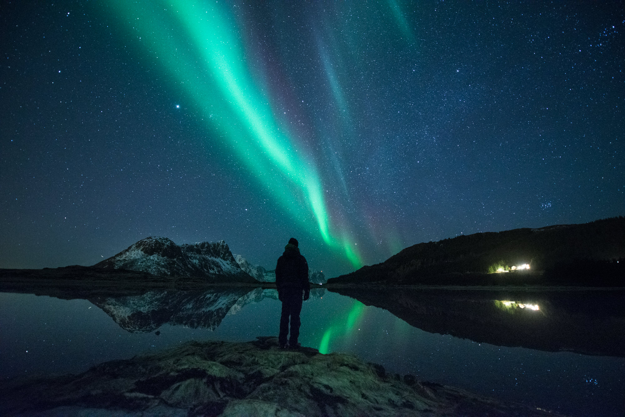 A man watches the northern lights over a lake