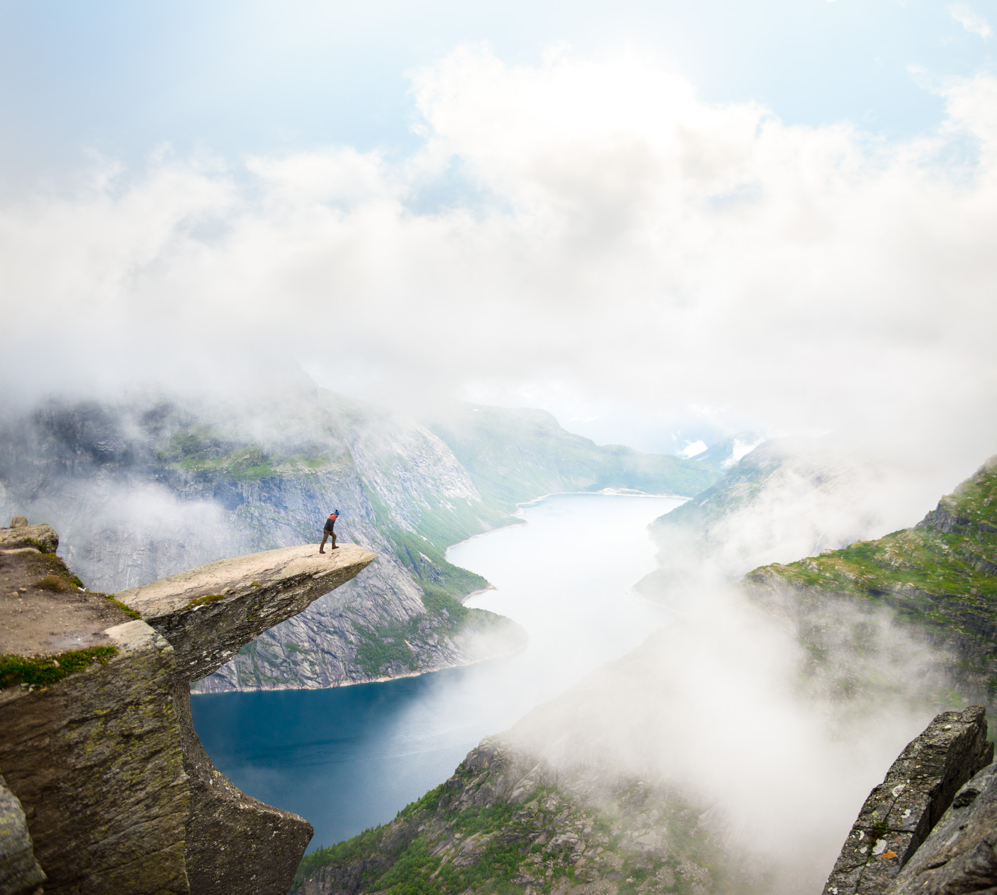 a man stands on Trolltunga looking over the edge