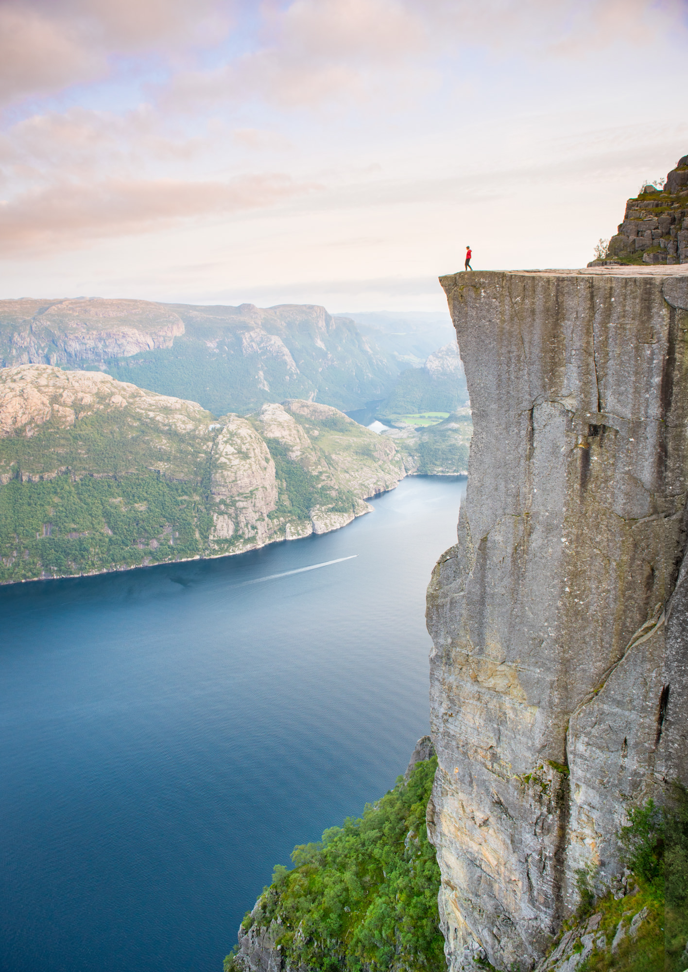 A man walks on top of Pulpit rock at sunset
