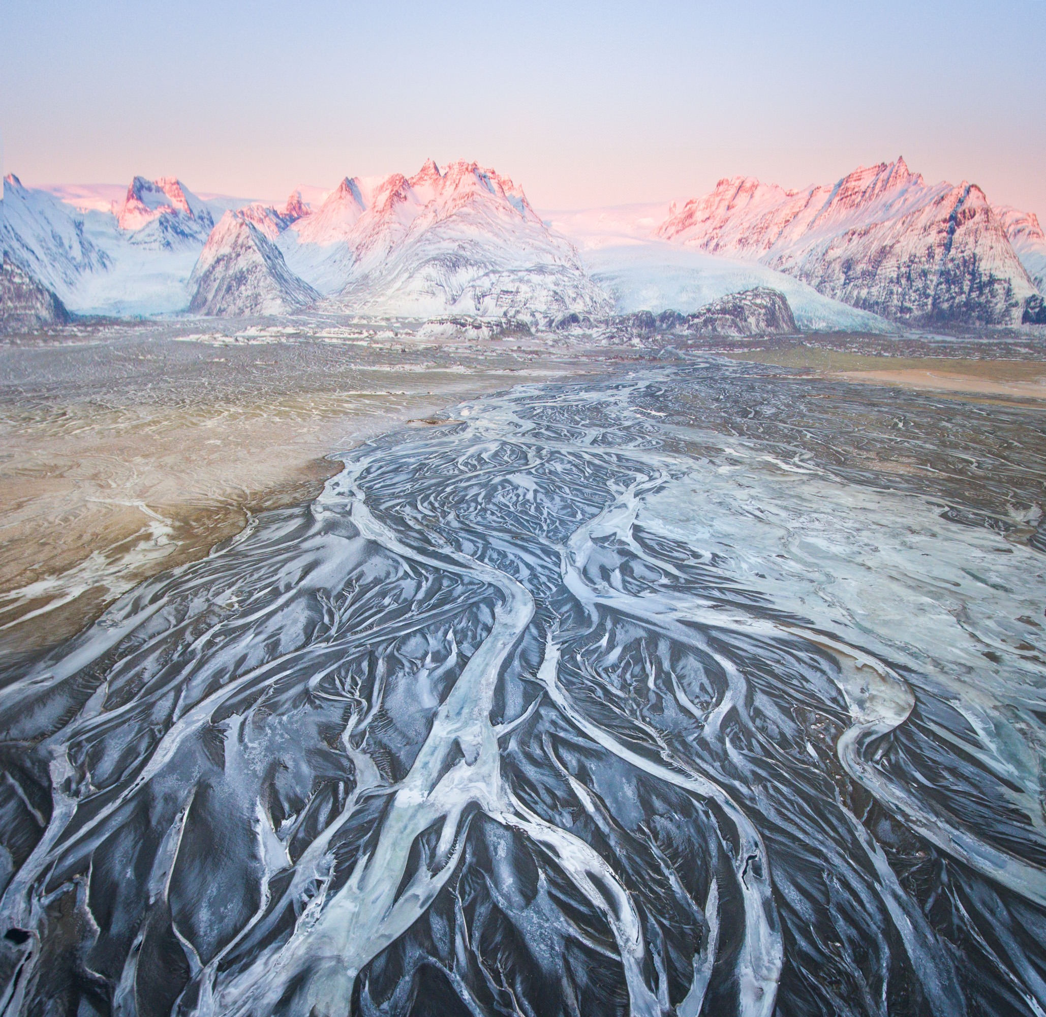 Aerial of icy glacial rivers in iceland with mountains behind