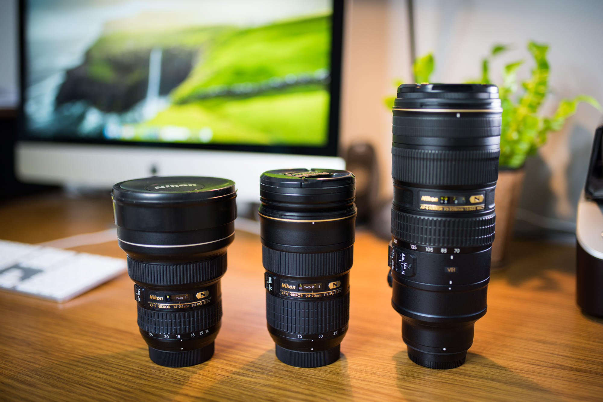 Three of the best lenses for landscape photography sitting on a desk