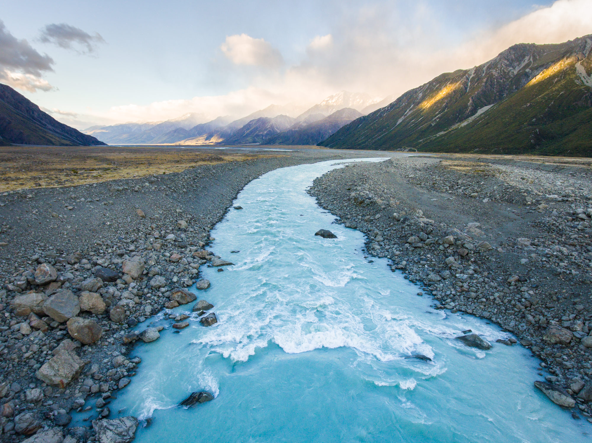 A blue glacial river in mountainous valley