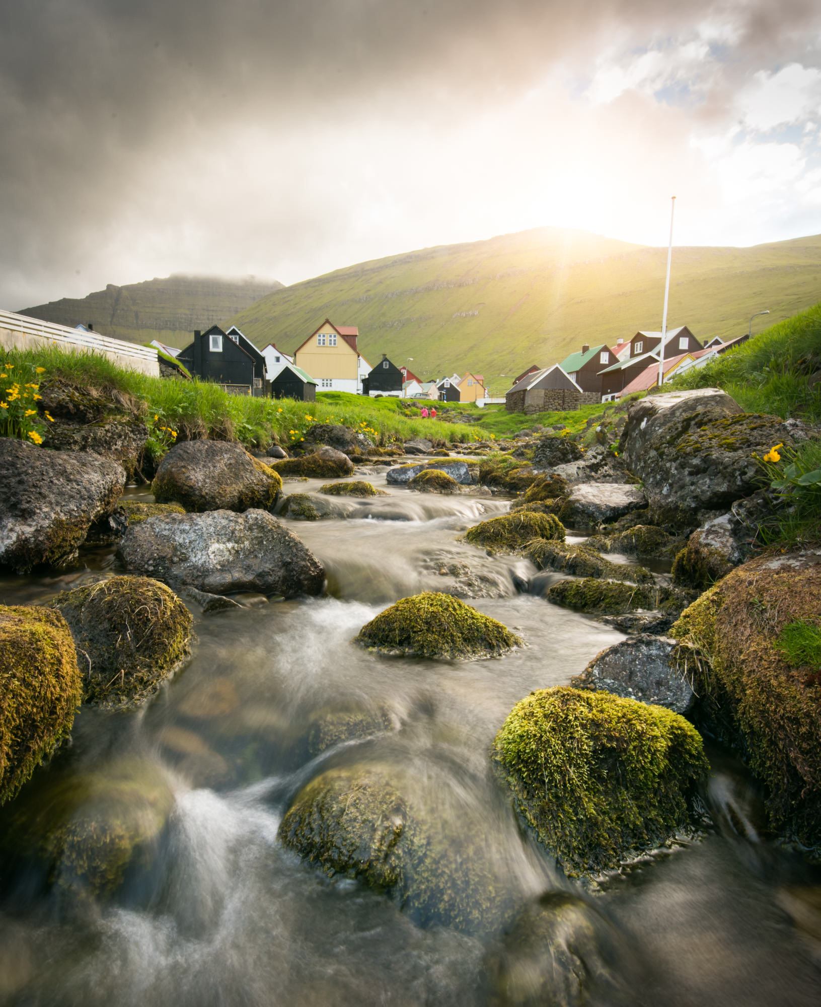A small fishing village in the Faroe Islands with a stream running through