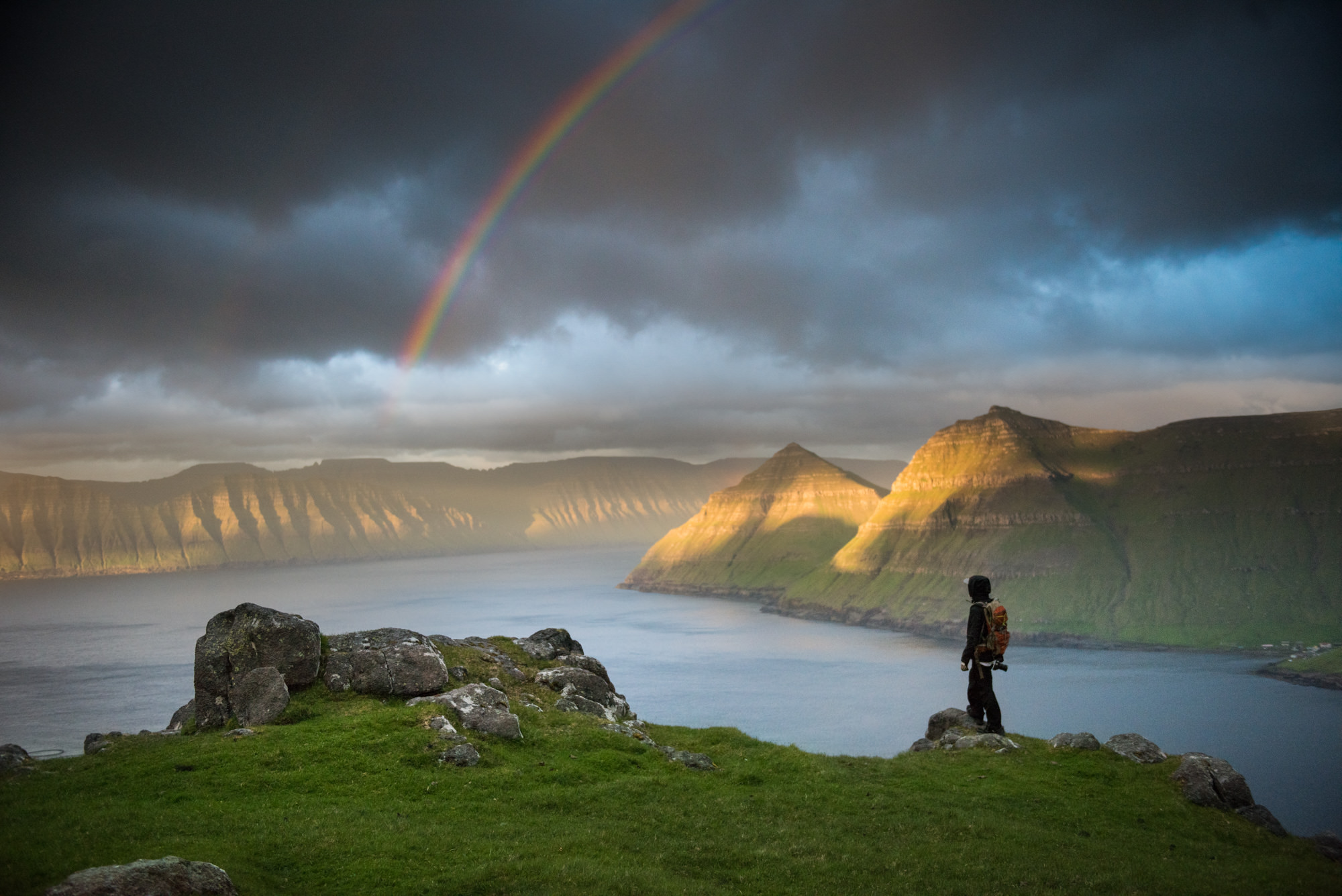 Faroe Islands Fjords in dramatic light with a rainbow and a man looking out