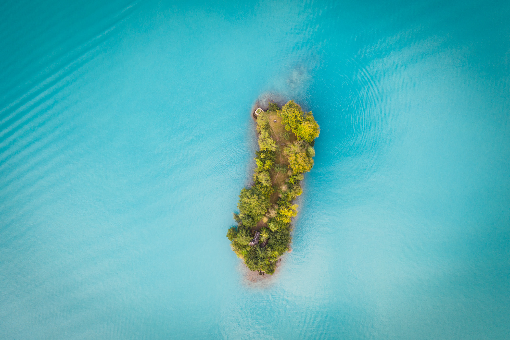 A small island from above in a lake with bright blue water