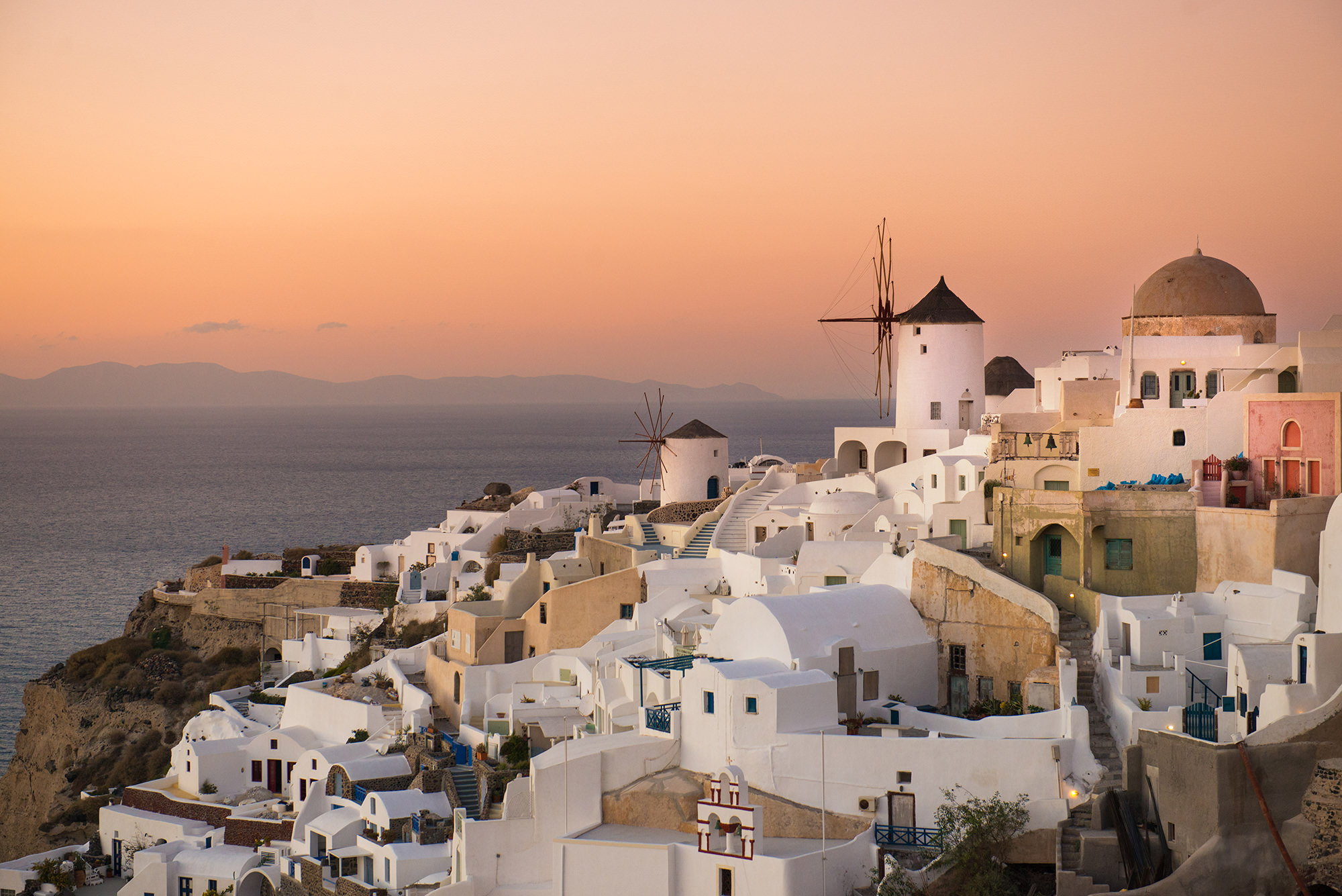 A beautiful sunset over a village of white buildings in Greece above the ocean.