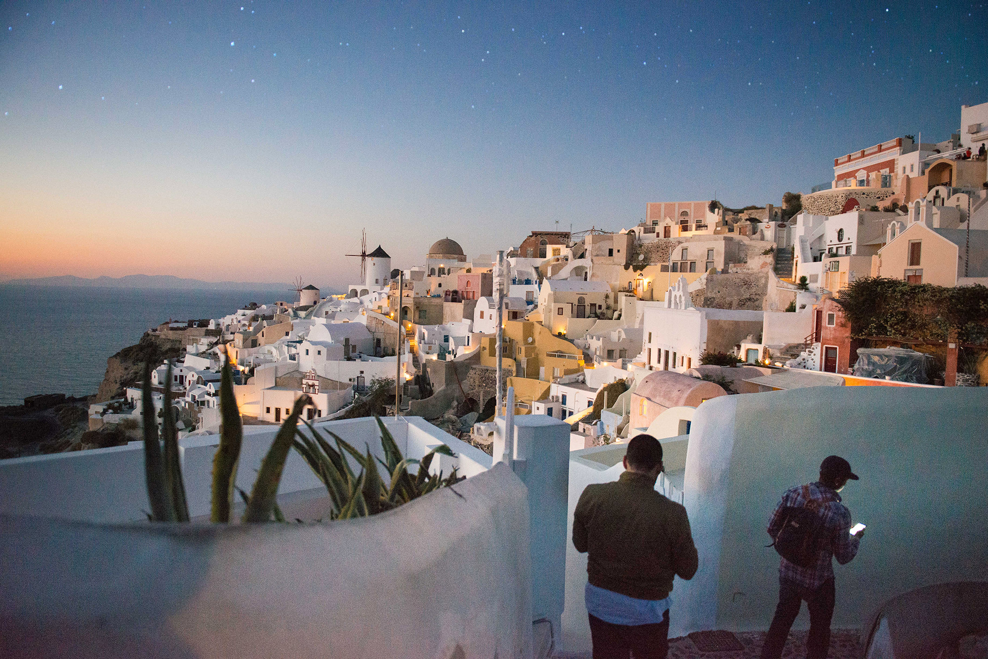 Night skies over a Greek village on a cliff side next to the sea