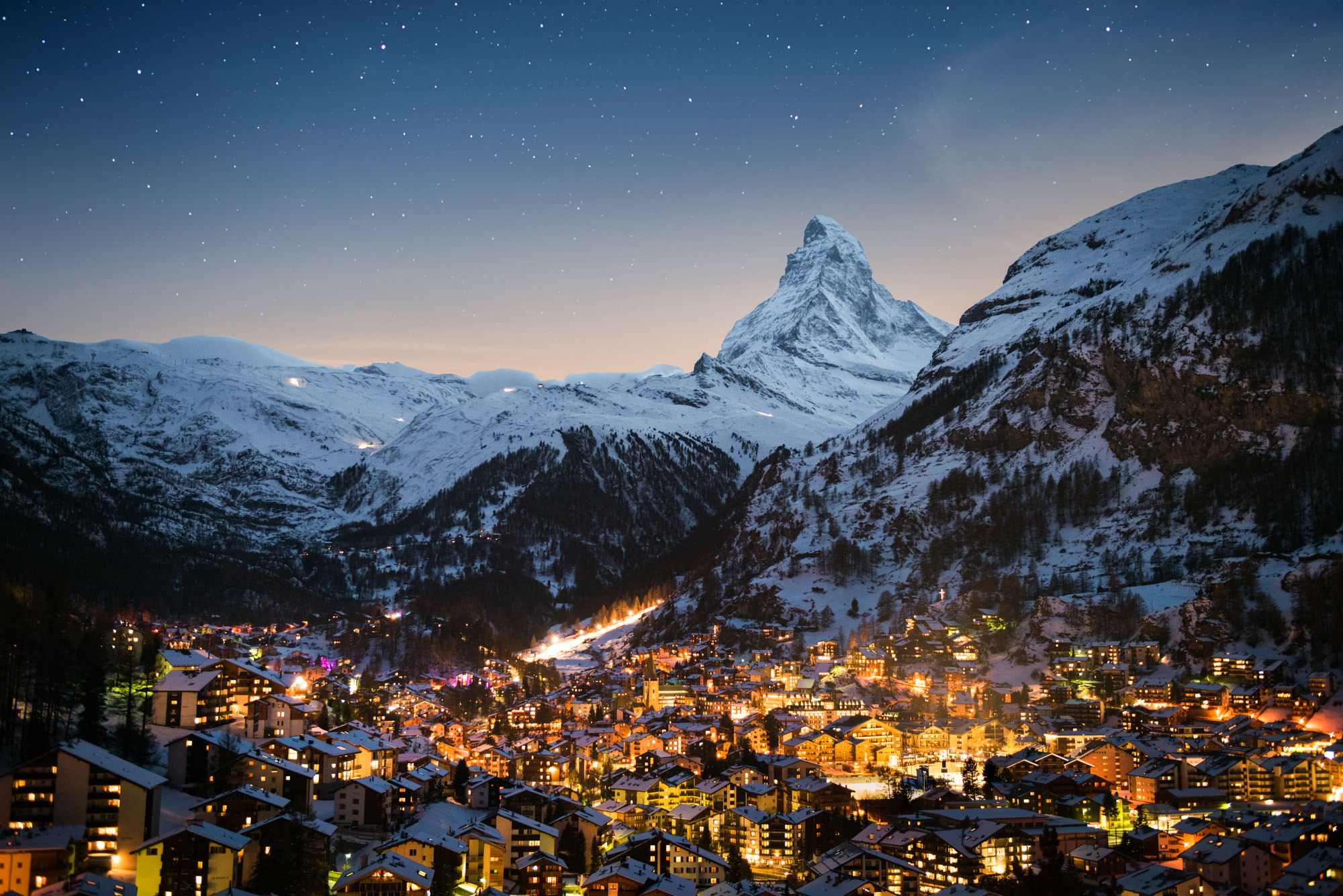 A magical winter wonderland snowy town in the mountains with the Matterhorn behind at night.