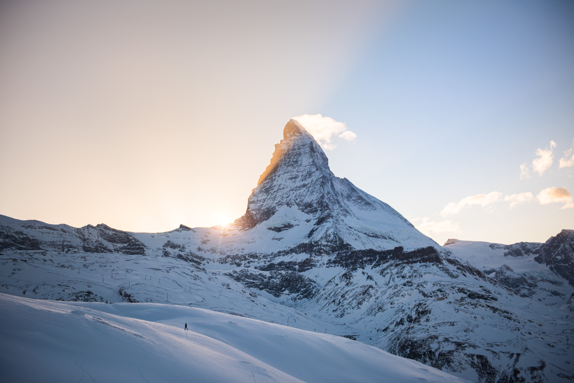 The sun setting behind the huge mountain the Matterhorn with a man walking in front