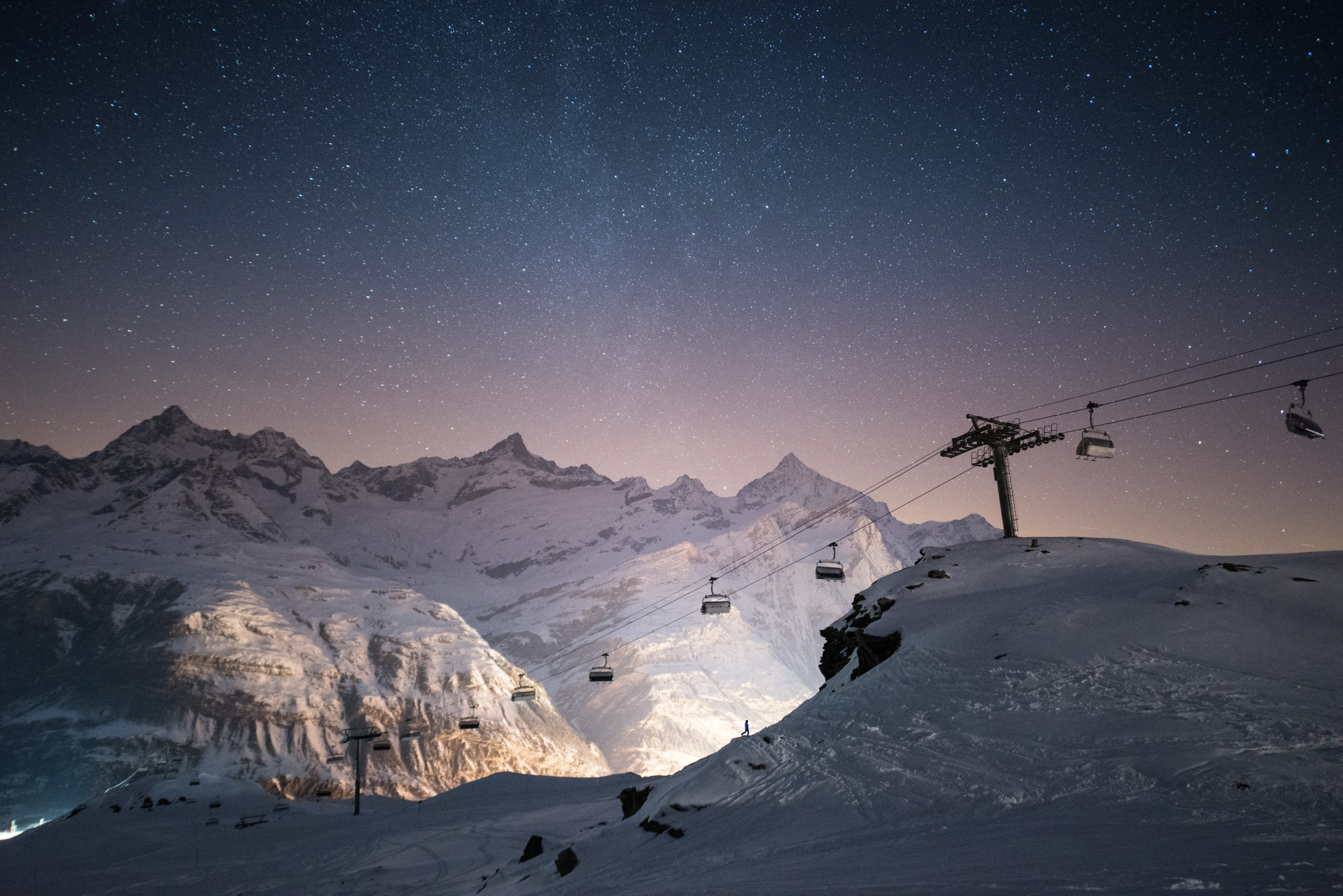 A starry night sky in the snowy mountains with a small figure walking in front of ski lifts