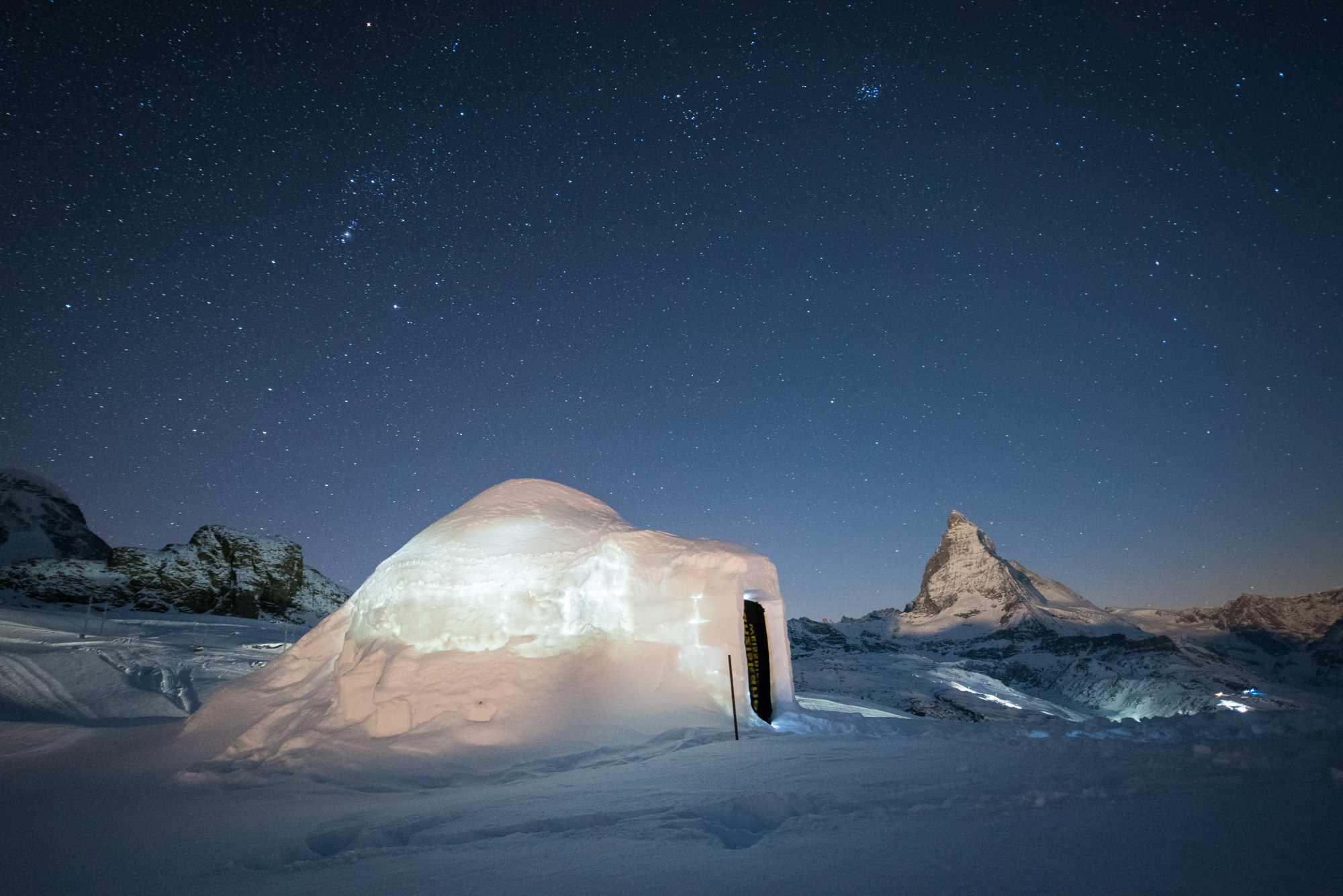 An igloo in the snow at night with the matterhorn behind