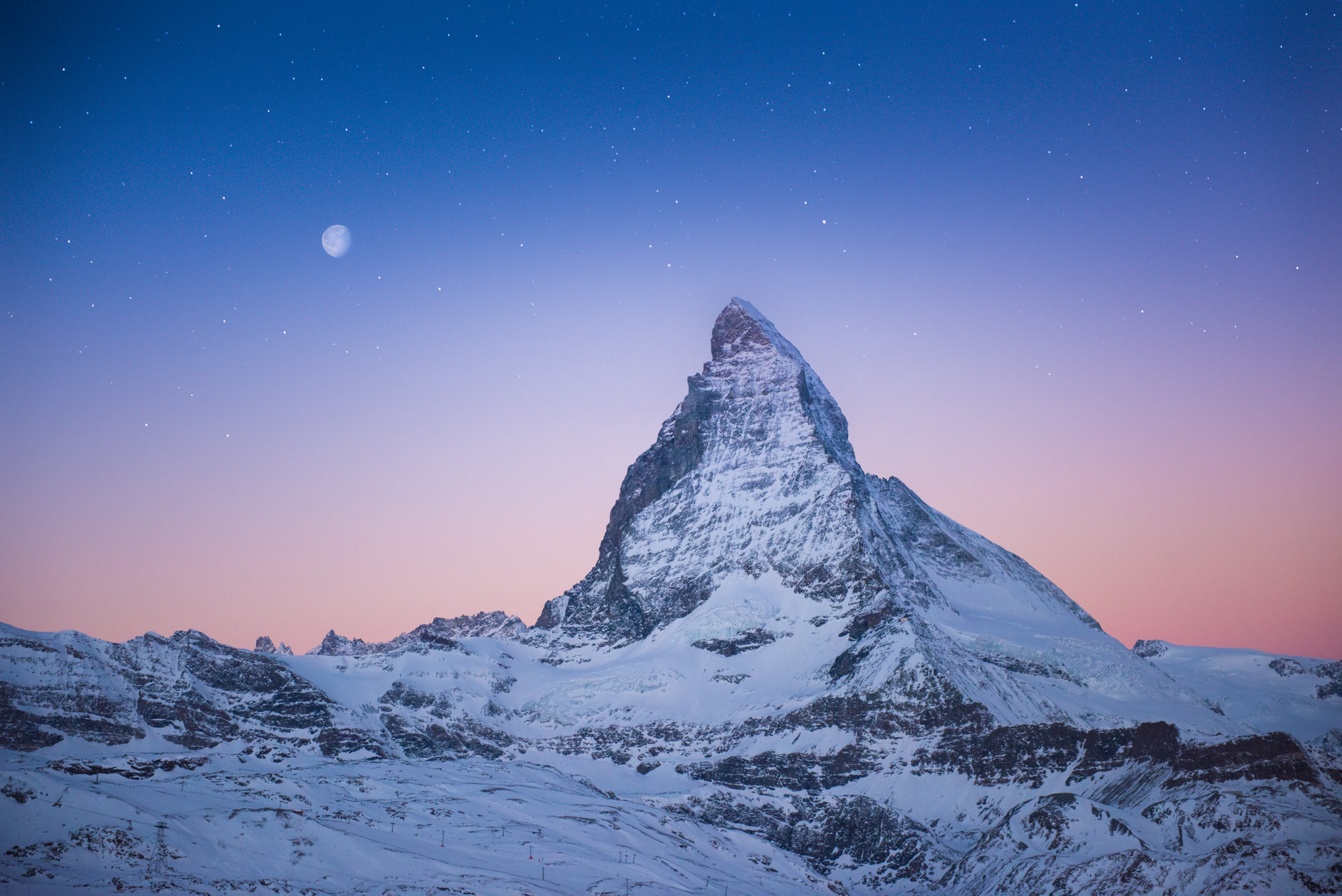 A triangular shaped mountain next to the moon at dusk