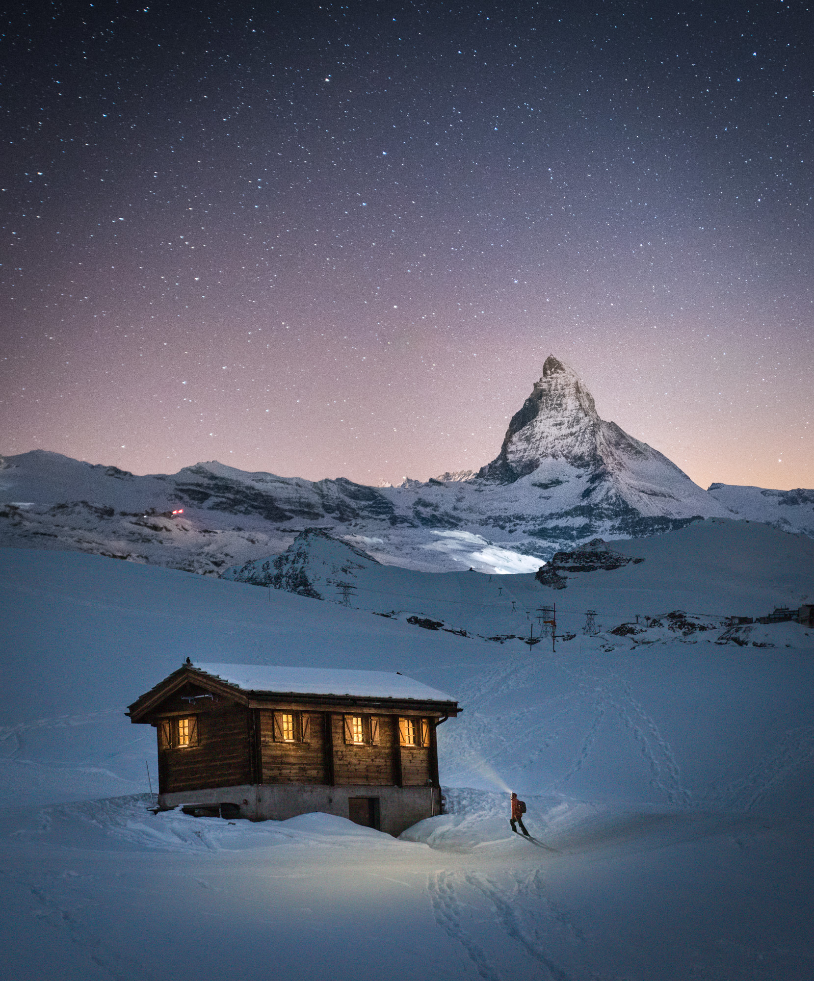 A man walking into a log cabin in the snow in the mountains at night