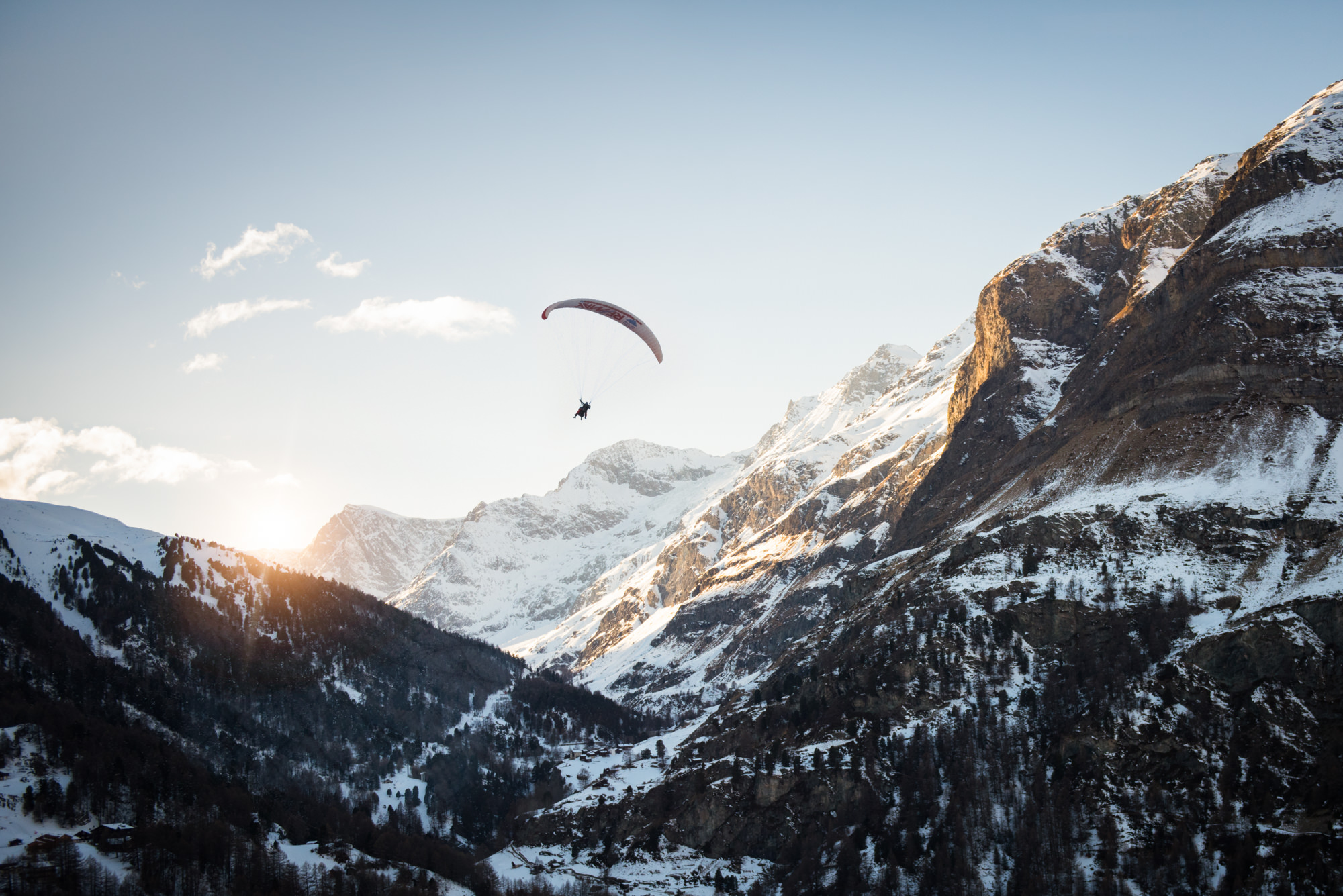 A paraglider flying through a snowy mountain at sunset