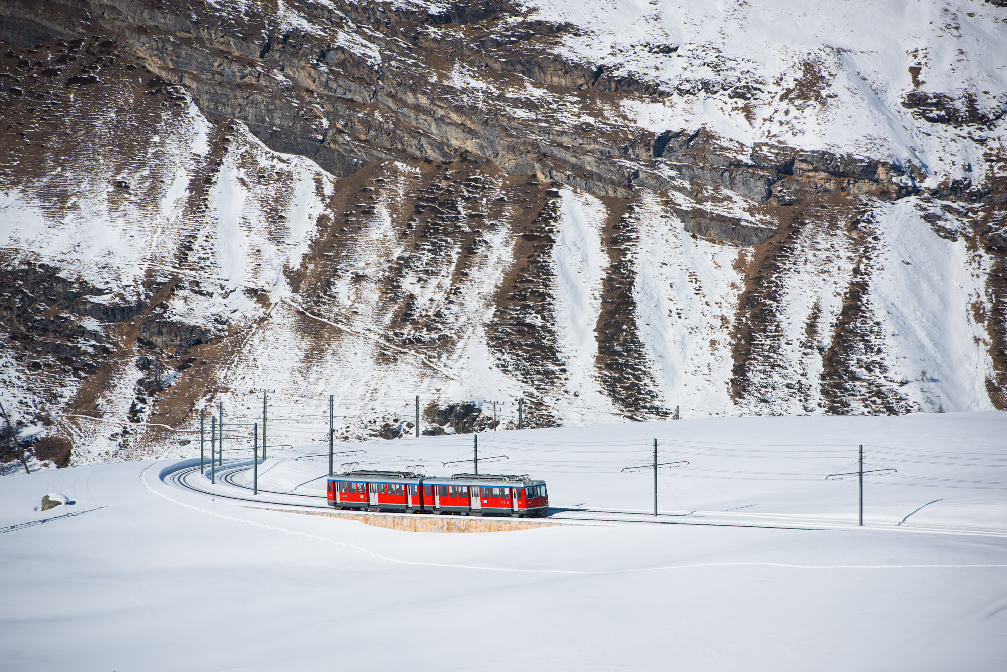 A red train in a snowy mountain scene