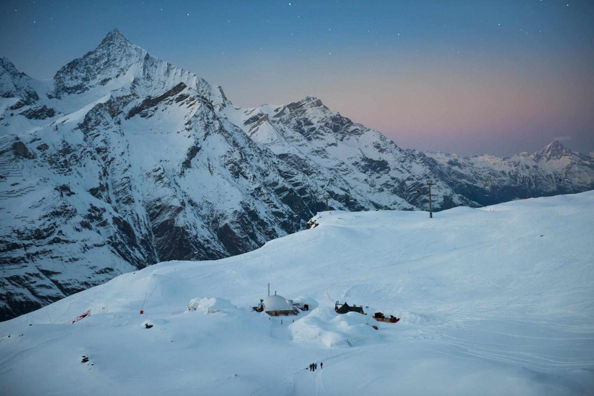 A snowy mountain scene at dusk